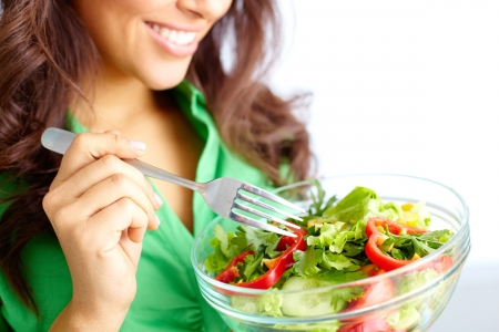 Close-up of pretty girl eating fresh vegetable salad photo