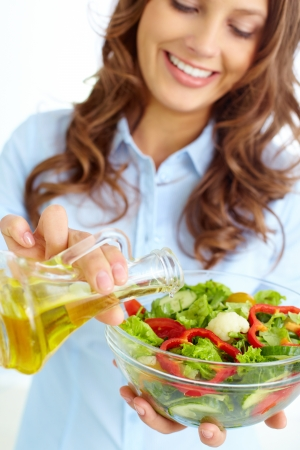 Close-up of smiling female pouring olive oil into vegetable salad photo