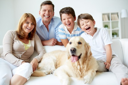 Portrait of happy family with their pet having good time at home Stock Photo