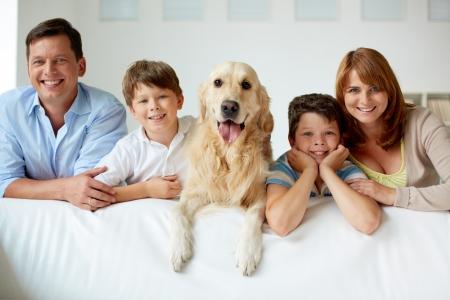 Retrato de familia feliz con su mascota mirando a la c�mara photo