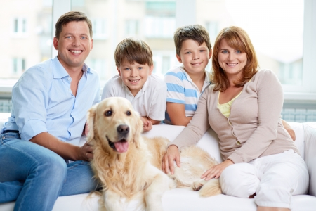 Cheerful family with their pet sitting on sofa at home photo