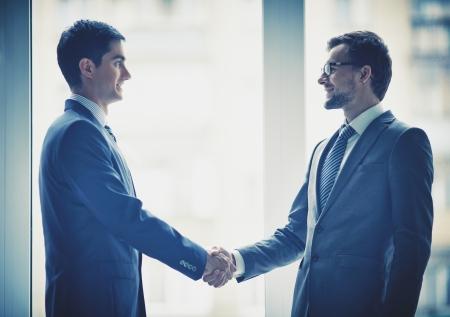 integridad: Foto de los hombres de negocios exitosos apretón de manos después del reparto llamativo Foto de archivo