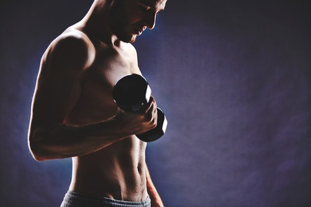 Image of handsome man with bare torso doing exercise with barbell photo