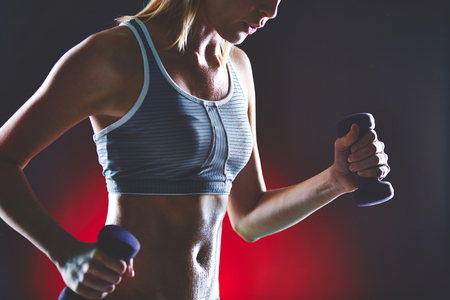 activewear: Body of slim female in activewear doing physical exercise with dumbbells