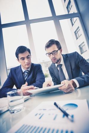 revisando documentos: Imagen de dos hombres de negocios jovenes que discuten el documento en el touchpad a satisfacer