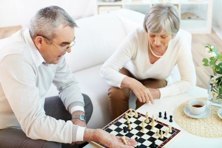 Portrait of senior couple playing chess at leisure  photo