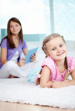caucasian woman: Ritratto verticale della figlia sdraiata sul pavimento con la madre su sfondo Archivio Fotografico