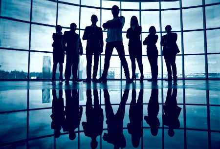standing against: Business team standing against window with leader in front