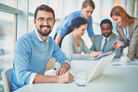 Groep van zakelijke partners te praten over ideeën met hun leider op de voorgrond