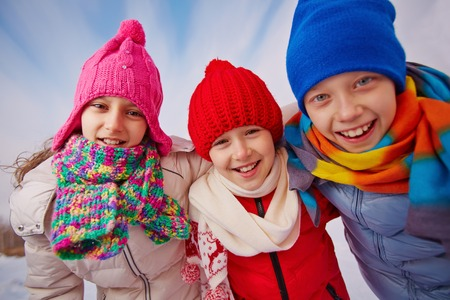 Joyful kids in winterwear looking at camera with smiles outside photo