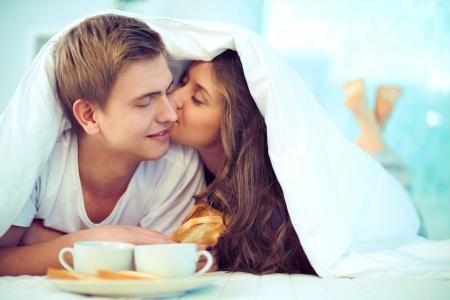 couple au lit: Couple en appr�ciant un de l'autre tout en prenant le petit d�jeuner au lit