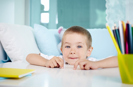 lad: Adorable lad looking at camera while sitting by table