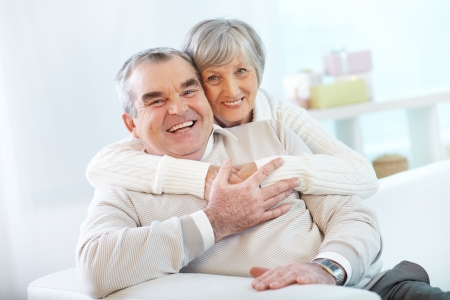 Portrait of a happy senior woman embracing her husband and both looking at camera Banco de Imagens