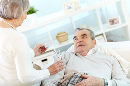 Portrait of mature woman giving tablets and glass of water to her sick husband at home Stock Photo - 25254666