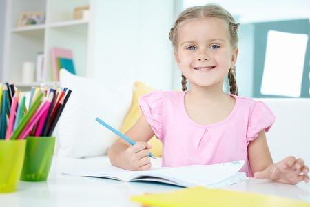colegiala: Ni�a linda que se sienta en la mesa con l�pices de colores y copybook abierto delante de ella Foto de archivo