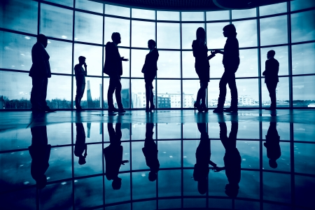 associates: Several colleagues communicating in office against window
