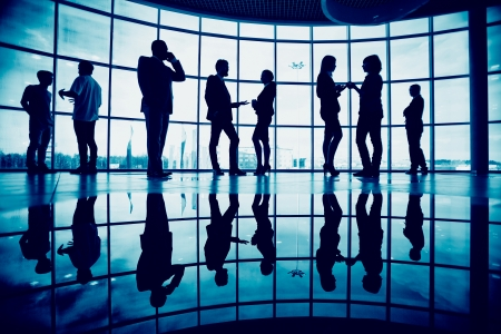 Groep collega's te communiceren in het kantoor tegen venster