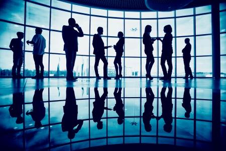 occupations and work: Gruppo di colleghi che comunicano in carica contro la finestra