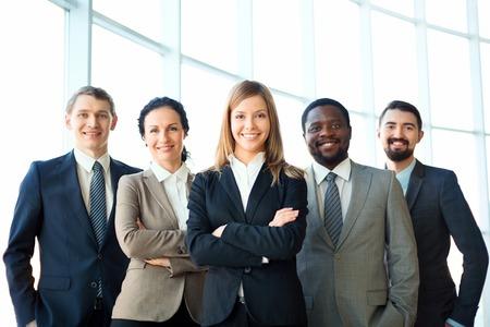 Groep van zakelijke partners kijken naar de camera met een glimlach, mooie leider voor Stockfoto