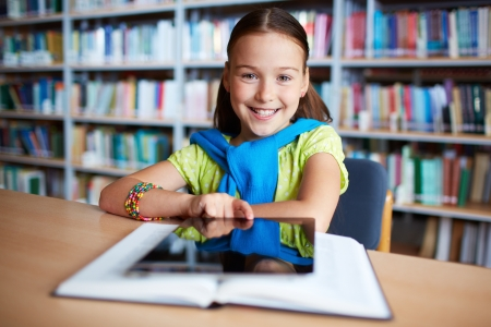 Portrait of cheerful schoolgirl looking at camera while sitting in library photo
