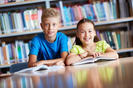 learner: Portrait of cute schoolchildren looking at camera while sitting in library