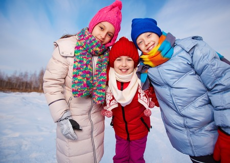 Joyful kids in winterwear looking at camera while having happy time outside photo