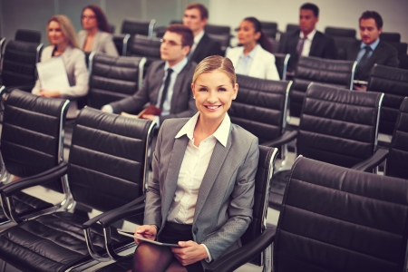 Image of business people sitting in rows at seminar with pretty woman in front photo