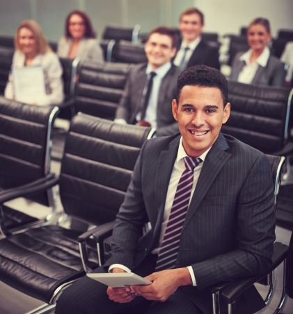 Image of smiling businessman sitting in row with his colleagues on background photo