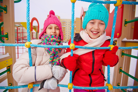 winterwear: Happy girls in winterwear looking at camera while having fun on playground