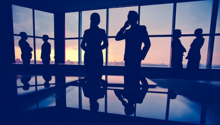 Silhouettes of several colleagues communicating in office photo