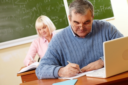 computer lesson: Senior man in eyeglasses carrying out written task in classroom