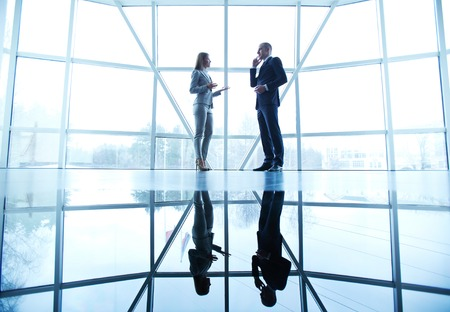Image of successful businessman and businesswoman communicating at meeting