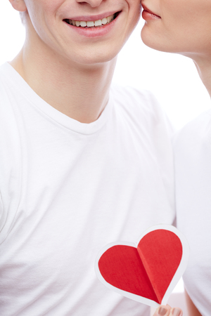 committed: Close-up of amorous young girl with red paper heart by her boyfriend cheek