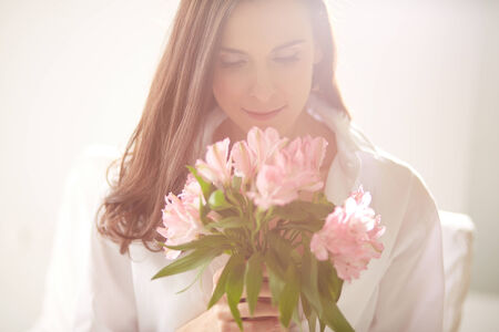 Portrait of lovely lady looking at bunch of flowers in her hands photo