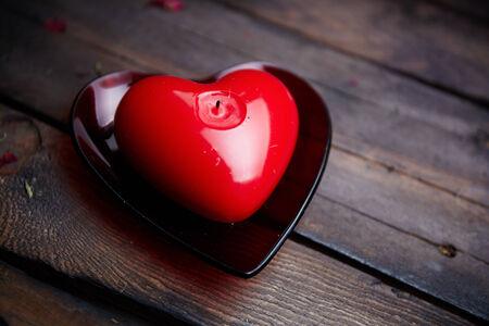 bougie coeur: Image de rouge en forme de coeur bougie sur bois
