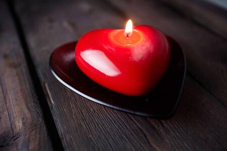 bougie coeur: Image de coeur rouge en forme de bougie allumée sur bois Banque d'images