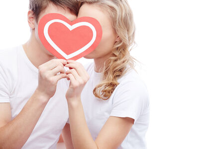 inlove: Portrait of amorous young couple holding red heart by their faces Stock Photo