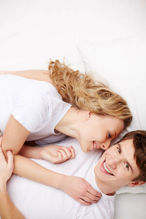 committed: Portrait of happy guy looking at camera with his girlfriend lying near by