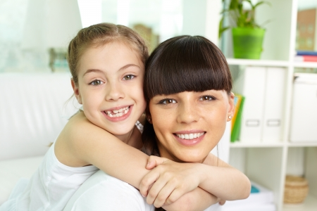 committed: Portrait of happy girl and her mother looking at camera with smiles