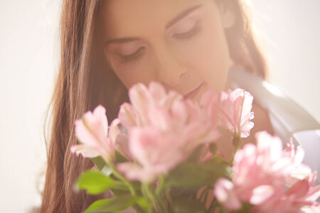Portrait of lovely lady looking at flowers and smelling them photo