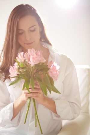 Portrait of lovely lady looking at bunch of pink lilies in her hands photo