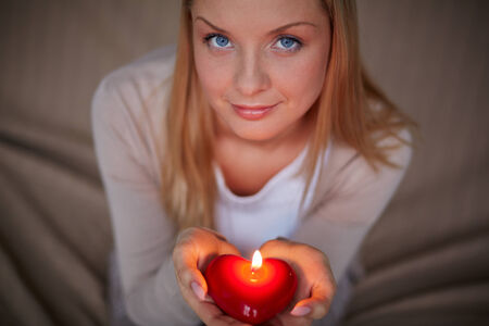 Image of smiling female with burning candle looking at camera Stock Photo