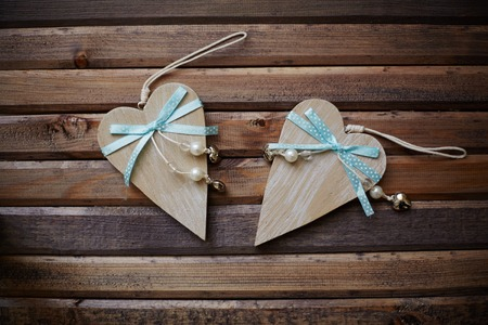 corazones: Image of wooden hearts with blue ribbons and pearls on wooden