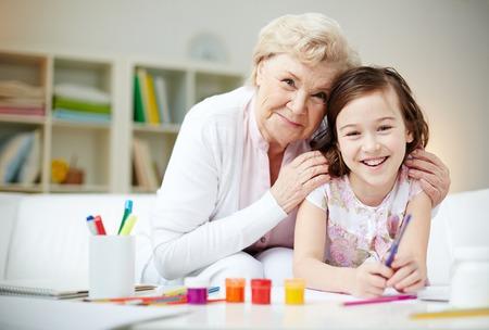 Portret van een gelukkig meisje en haar grootmoeder kijken camera thuis