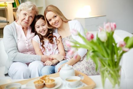 Portret van een gelukkig meisje, haar moeder en grootmoeder kijken naar de camera thuis