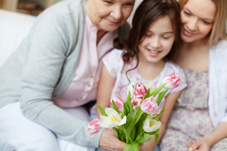 mothers group: Bunch of tulips held by senior woman with her daughter and granddaughter near by Stock Photo