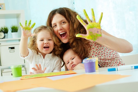 Portrait of a happy family having fun painting with palms and fingers photo