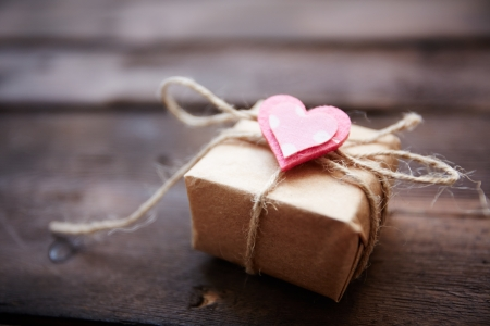 Image of valentine giftbox with small pink heart on wooden background photo