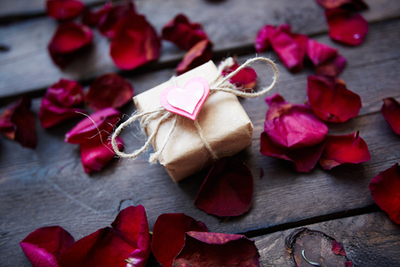 Image of valentine giftbox with small pink heart surrounded by rose petals photo
