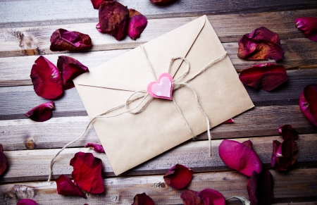 Image of letter of love with small pink heart surrounded by rose petals photo